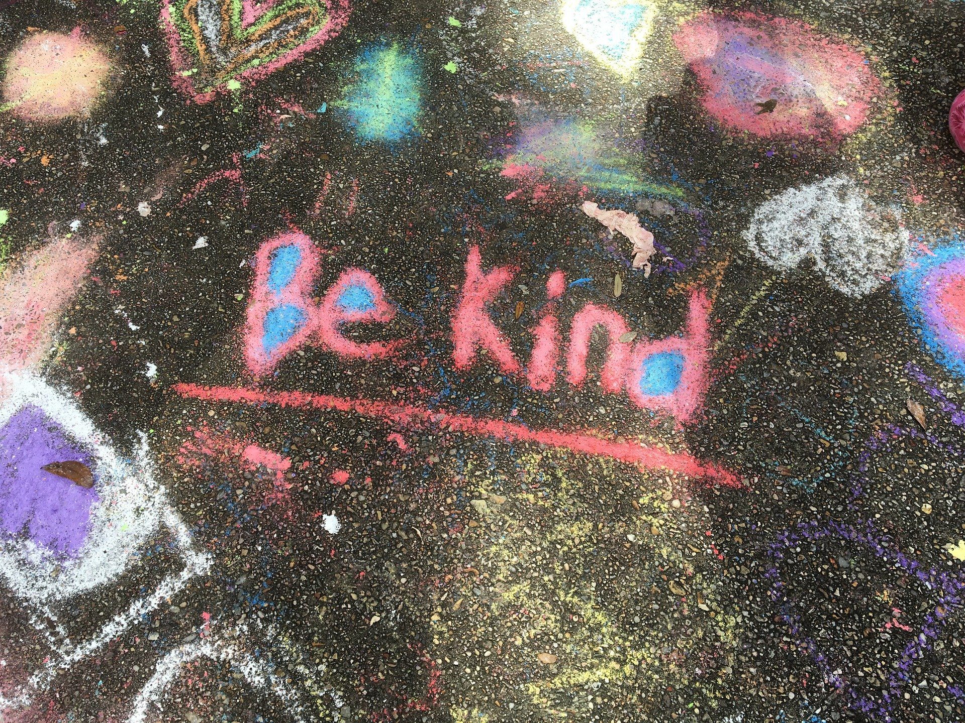 """""""Be kind"""" written in bright colors in chalk"""