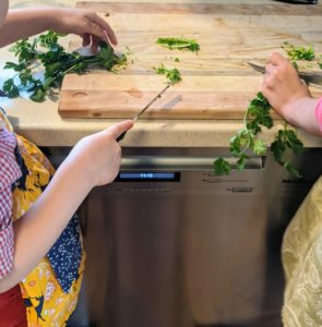 Children helping to cut greens on a cutting board