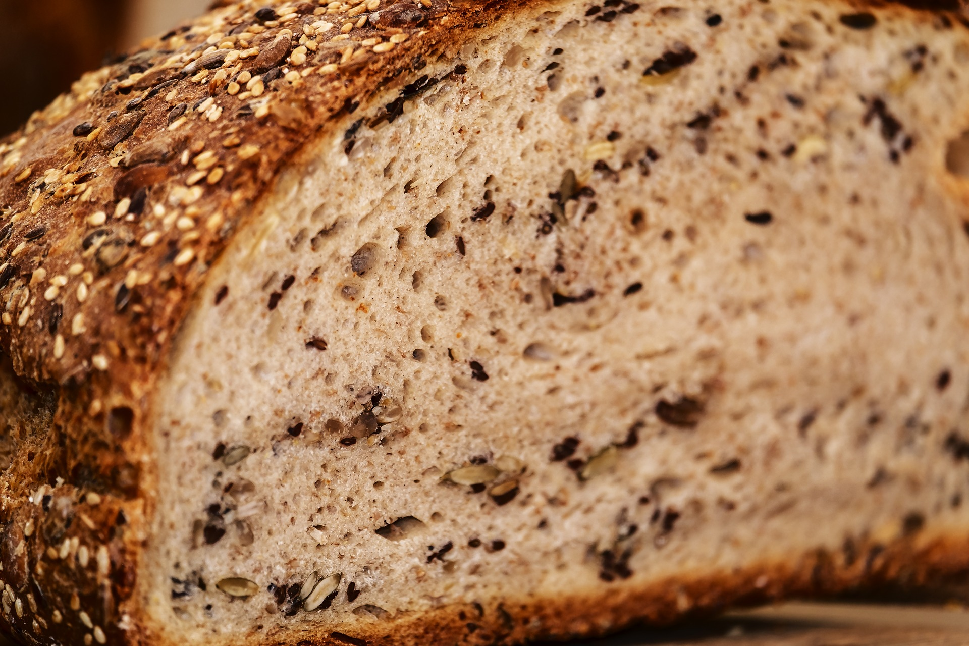 A close-up of a sliced loaf of seeded bread