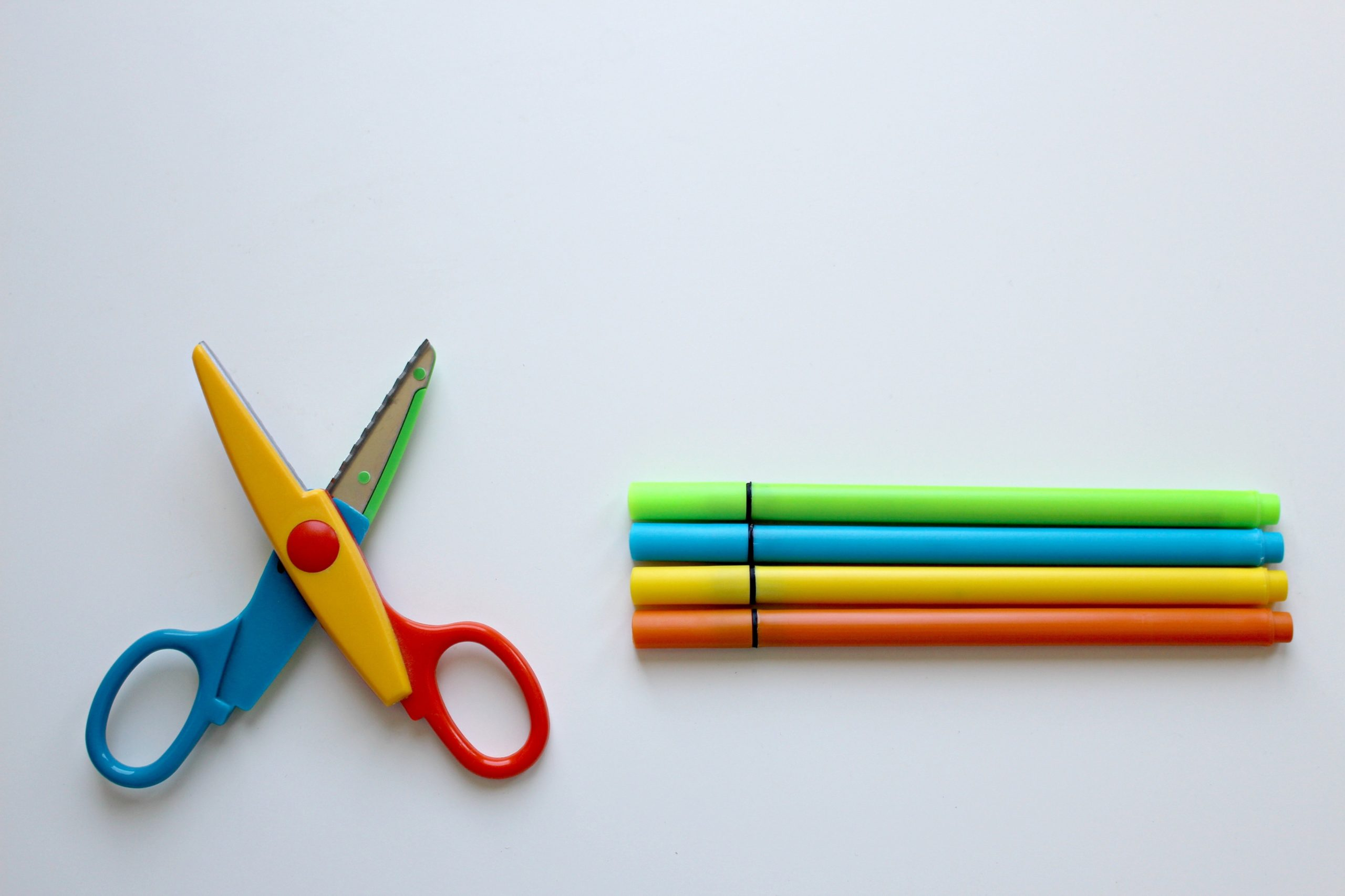A colorful pair of scissors next to a set of colored pens